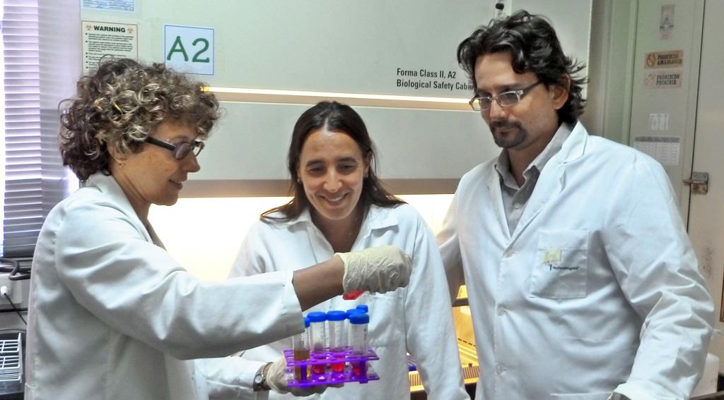 La doctora Andrea Gamarnik (izq.),  jefa del Laboratorio de Virología Molecular del Instituto Leloir y dos integrantes de su equipo, la doctora en bioquímica Claudia Filomatori y  el licenciado en genética Sergio Villordo, en el Cuarto de Bioseguridad donde estudian el virus del dengue.