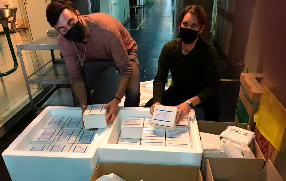 """Horacio Martín Pallarés (izq.) y Diego Ojeda, integrantes del Laboratorio de Andrea Gamarnik en el Instituto Leloir, preparan un lote de 10.000 determinaciones de """"COVIDAR IgG"""" para entregar a la Provincia de Buenos Aires."""